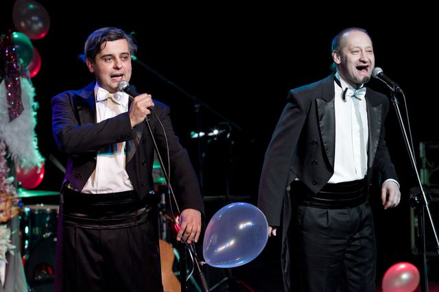 Dwaj mężczyźni, jeden z ciemnymi, siwiejącymi włosami, drugi - łysiejący blondyn, stoją przy mikrofonach i śpiewają. W ciemnym tle majaczą kolorowe balony, instrumenty i elementy garderoby. Artyści ubrani są jednakowo – w czarne fraki i spodnie, białe koszule z muszkami, pasy smokingowe.