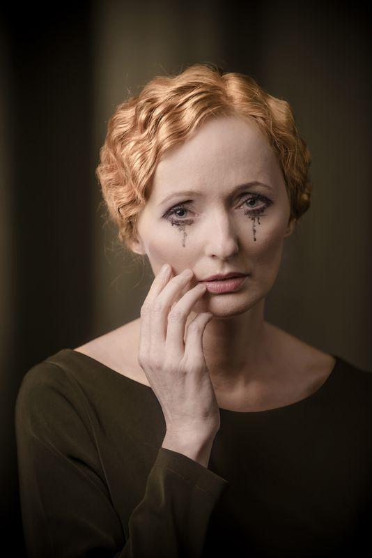 Portret Justyny Szafran kreującej rolę Kobiety. Ciemny strój kontrastuje z bladą twarzą, nieskazitelną cerę podkreśla delikatny makijaż, jedynym zgrzytem jest rozmazany tusz płynący z oczu. Artystka prawą dłonią lekko dotyka prawego policzka i okolicy ust, patrzy ze smutkiem. Ma rude, falujące włosy bez grzywki, spięte z tyłu głowy. Kolorystyka ciemnej zieleni i sepii.