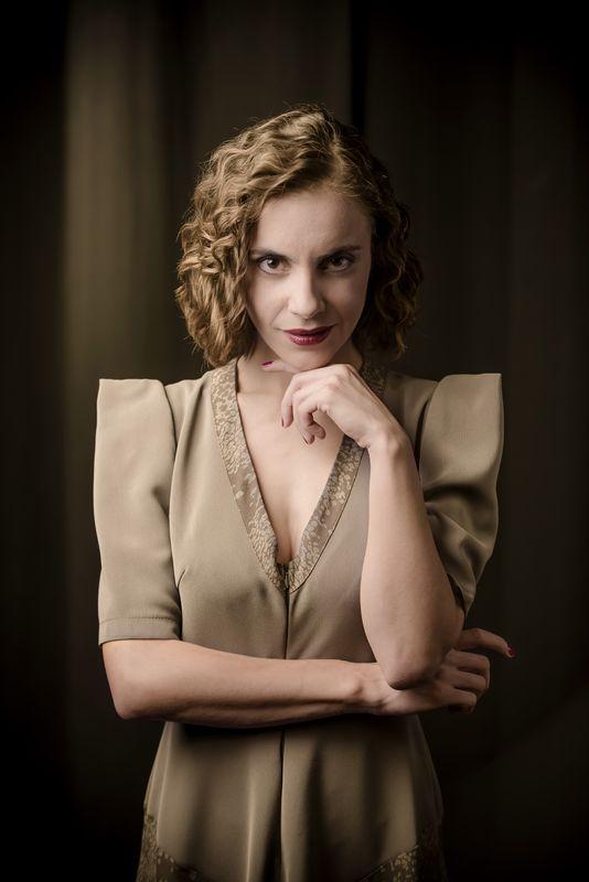 Portret Justyny Antoniak, kreującej rolę Małgorzaty. Ubrana w oliwkową sukienkę z dekoltem karo, jest szatynką, ma półdługie, falujące włosy, bez grzywki. Patrzy wprost, lekko się uśmiecha. Kolorystyka beżu i sepii, z zaznaczoną czerwienią uszminkowanych ust i lakieru na paznokciach.