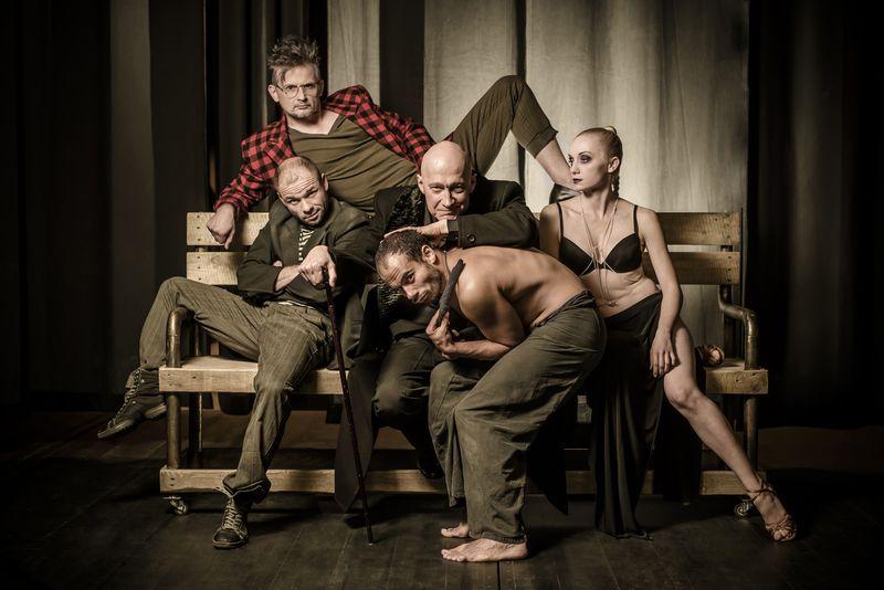 Zdjęcie grupowe odtwórców ról: Helli, Wolanda, Korowiowa, Asasella i Behemota. Na ławce siedzą, od lewej: Bartosz Picher (Asasello), Tomasz Wysocki (Woland) i Ewelina Adamska-Porczyk (Hella). Za nimi, na oparciu, bokiem i w pozycji półleżącej znajduje się Błażej Wójcik (Korowiow), a półnagi, zgięty wpół Mikołaj Woubishet (Behemot), przycupnął przed Wolandem. Zdjęcie ma kolorystykę oliwkowej sepii, wyróżnia się na nim czerwień marynarki Korowiowa.