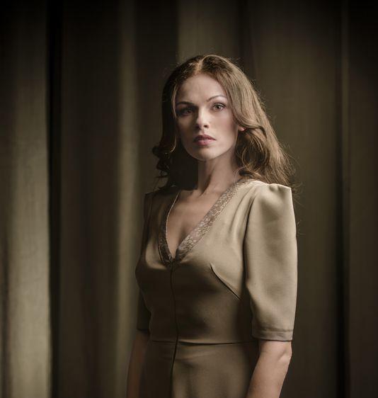 Portret Magdaleny Szczerbowskiej, kreującej rolę Małgorzaty. Ubrana w oliwkową sukienkę z dekoltem karo, jest brunetką, ma długie, lekko falujące włosy, bez grzywki. Patrzy wprost, ma poważny wyraz twarzy, urodę podkreśla lekki, naturalny makijaż. Kolorystyka beżu i sepii.
