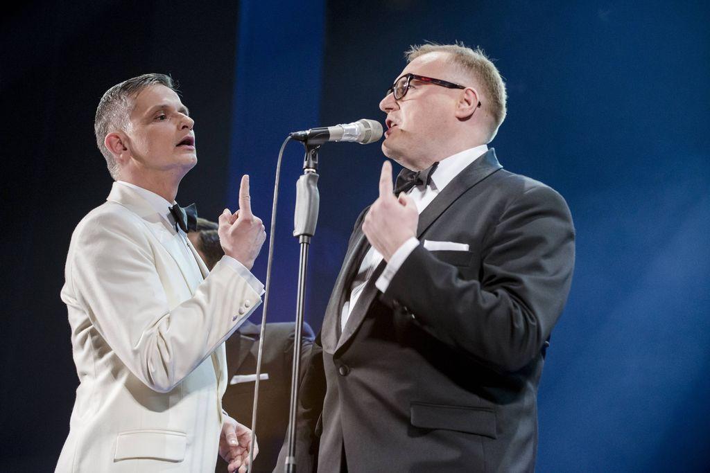Przy mikrofonie stoją dwaj mężczyźni – szpakowaty w białej marynarce, koszuli i muszce i blondyn w ciemnym garniturze, białej koszuli, również w muszce. Frank Sinatra i Konferansjer wykonują ten sam gest, mają wzniesione dłonie, jeden prawą, drugi lewą, z wyprostowanym, wskazującym palcem. Konferansjer mówi coś, lub śpiewa do mikrofonu, Sinatra patrzy na niego.