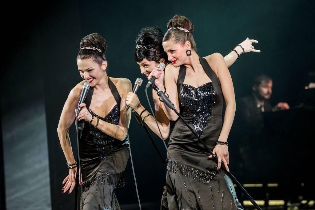 Trio śpiewających artystek, w tanecznych pozach, z mikrofonami w dłoniach, na ciemnym tle, z pianistą widocznym z prawej strony. Uśmiechnięte Sisters ubrane są w wieczorowe, obcisłe, czarne, wydekoltowane suknie, mają odkryte ramiona, błyszczącą biżuterię, diademy upięte przy dużych kokach.