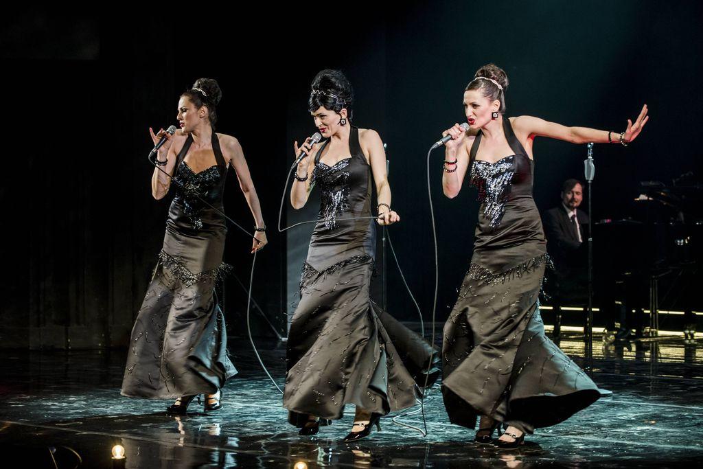 Trio śpiewających artystek, w tanecznych pozach, z mikrofonami w dłoniach, na ciemnym tle, z pianistą widocznym z prawej strony. Sisters ubrane są w wieczorowe, obcisłe, czarne, wydekoltowane suknie, mają odkryte ramiona, błyszczącą biżuterię, diademy upięte przy dużych kokach.
