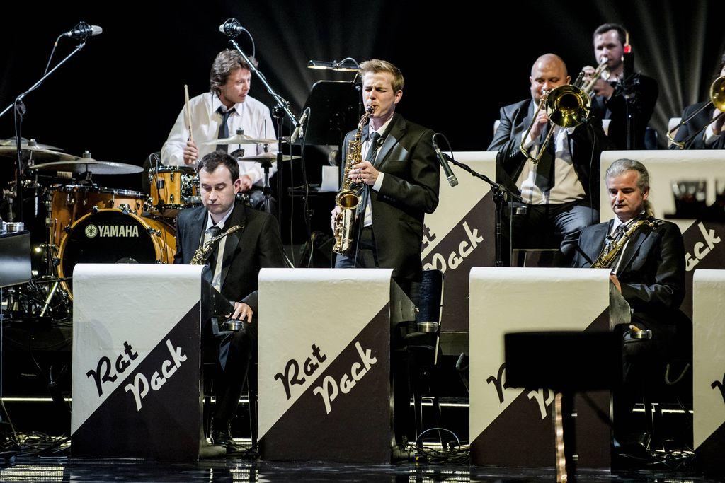 """Na zdjęciu znajduje się kilku muzyków wchodzących w sklad wieloosobowego zespołu, stylizowanego na big-band epoki swingu. Siedzą za pulpitami z napisem """"Rat Pack"""", mają na sobie garnitury, białe koszule, krawaty. Pomiędzy dwoma muzykami z pierwszego rzędu, stoi saksofonista, z tyłu za nim widać perkusistę i trębaczy."""