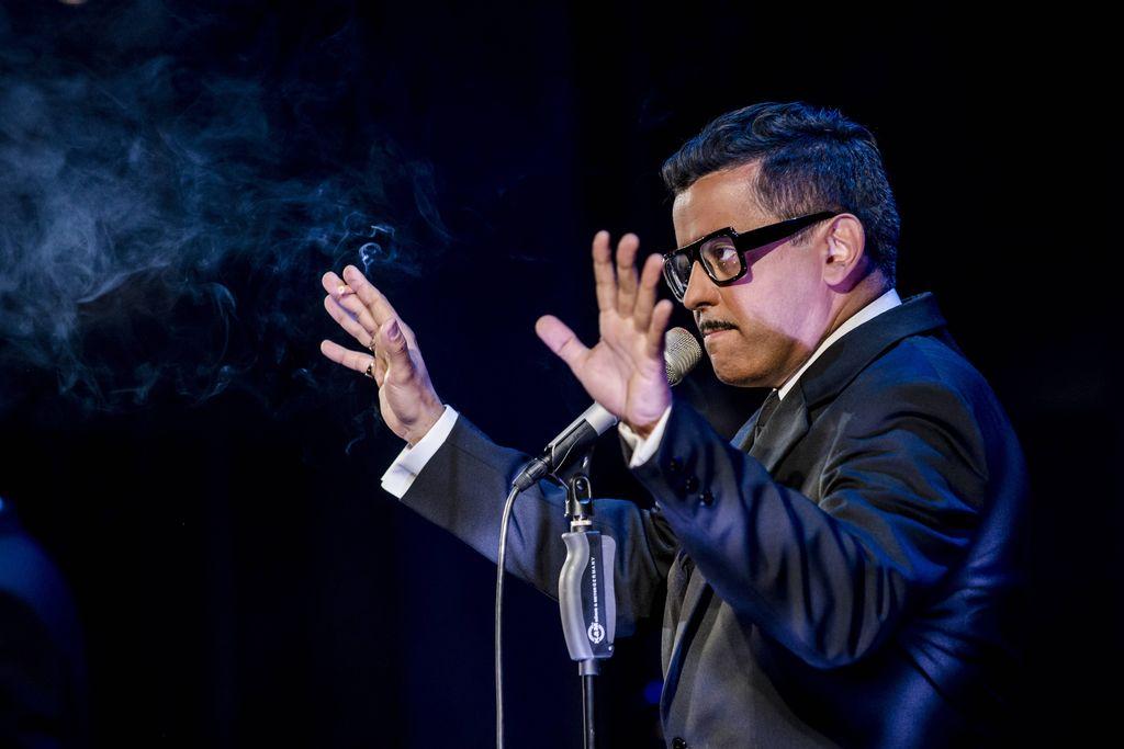 Przy mikrofonie stoi mężczyzna ubrany w elegancki czarny garnitur, białą koszulę i krawat. Sammy Davis Junior ma charakterystyczne okulary w czarnej oprawce i cienki wąsik. Obie dłonie ma uniesione na wysokości twarzy, w prawej trzyma zapalonego, dymiącego papierosa.