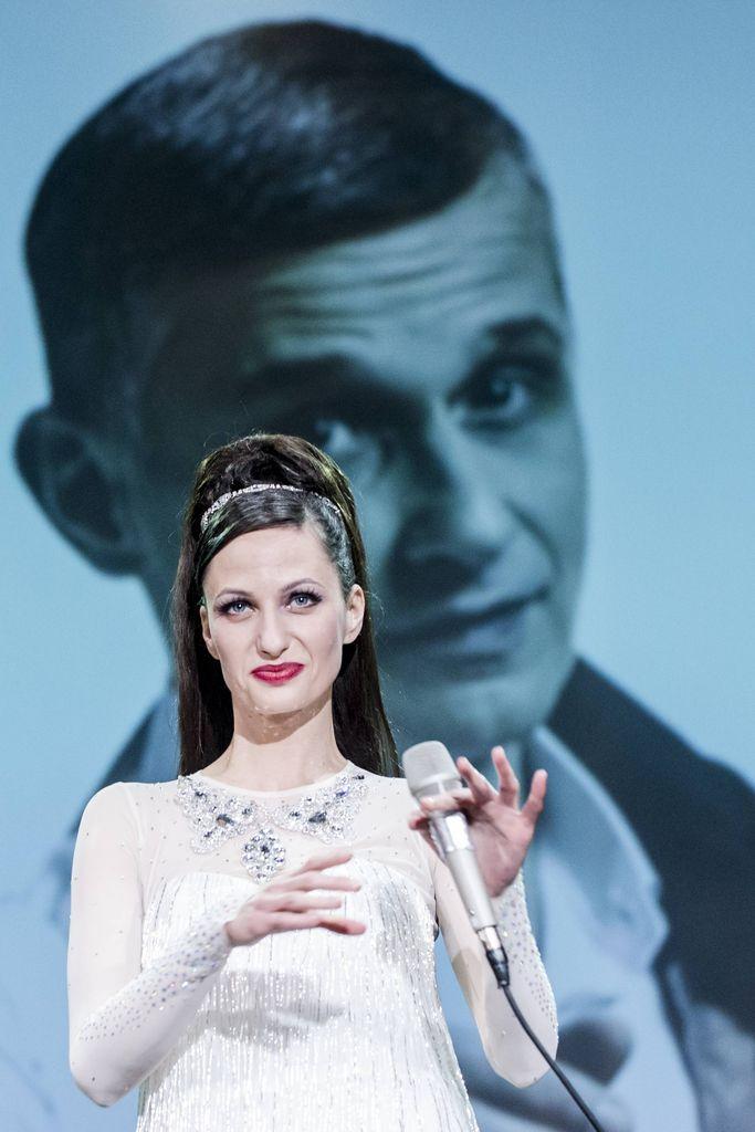 W centrum kadru znajduje się jedna z artystek tria Sisters, trzyma w lewej dłoni mikrofon. Ubrana jest w białą, naszywaną srebrnymi ozdobami sukienkę z długimi, transparentnymi rękawami. Ciemne włosy ma uczesane w kok, z tyłu rozpuszczone, ozdobione przy koku srebrnym diademem. W tle, na dużym ekranie, widoczna jest podobizna aktora kreującego Franka Sinatrę.
