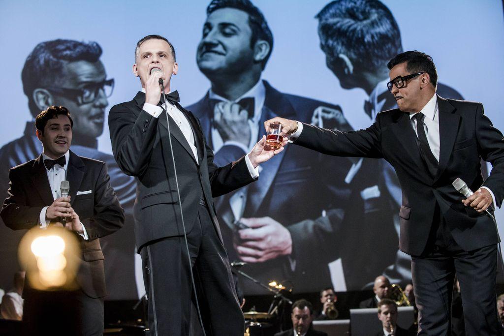 Na scenie trójka głównych bohaterów spektaklu, z lewej strony znajduje się Dean Martin, na środku śpiewający Frank Sinatra, z mikrofonem w prawej dłoni, z prawej strony widać Sammy`ego Davisa Juniora, który podaje Sinatrze szklaneczkę z brązowym płynem wewnątrz. Wszyscy ubrani są w czarne smokingi. Za nimi znajduje się duży, biały ekran, wyświetlają się na nim ci sami artyści, którzy są na scenie, ale w bardziej nieformalnej, zakulisowej sytuacji. W tle, u dołu widoczna jest orkiestra.