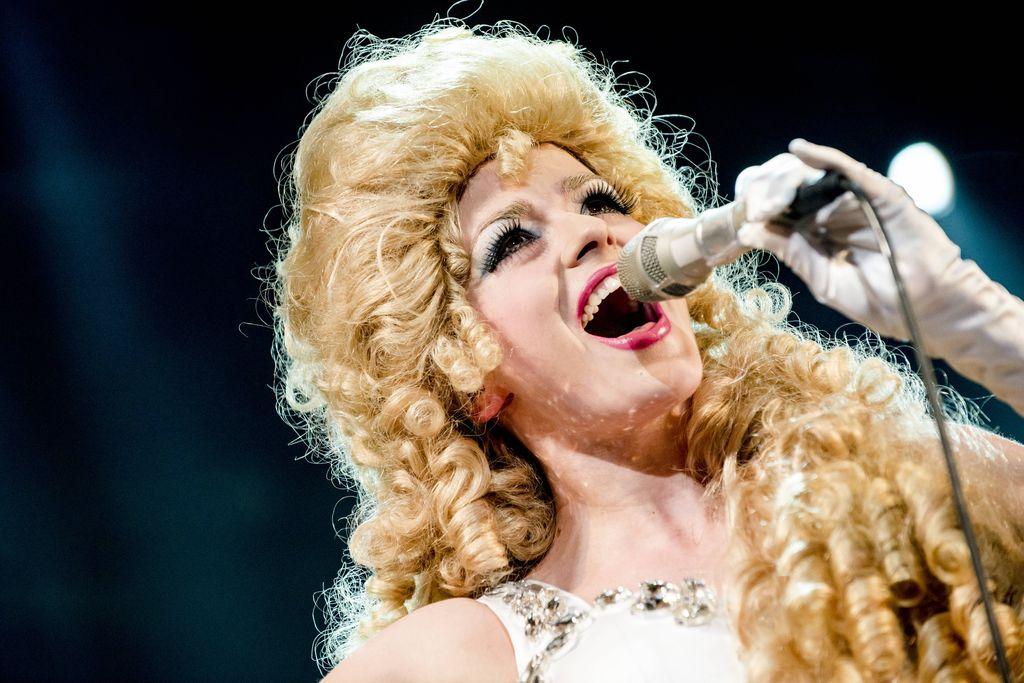 Podobizna artystki stylizowanej na Violettę Villas. Trzyma mikrofon w lewej dłoni w białej rękawiczce. Kobieta ekspresyjnie śpiewa, ma mocny makijaż, długie, sztuczne rzęsy i bujną perukę kojarzącą się jednoznacznie z atrybutem Violetty Villas.