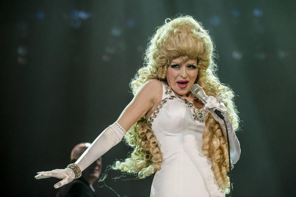 Na ciemnozielonym tle znajduje się artystka stylizowana na Violettę Villas. Stoi w tanecznej pozie, z mikrofonem w lewej dłoni, ma na sobie białą, obcisłą, wieczorową suknię, ozdobioną przy dekolcie błyszczącymi dżetami. Na rękach ma długie, białe rękawiczki, na prawym przegubie błyszczy gruba bransoletka. Kobieta śpiewa, ma zalotny wyraz twarzy, mocny makijaż i bujną perukę kojarzącą się jednoznacznie z atrybutem Violetty Villas.