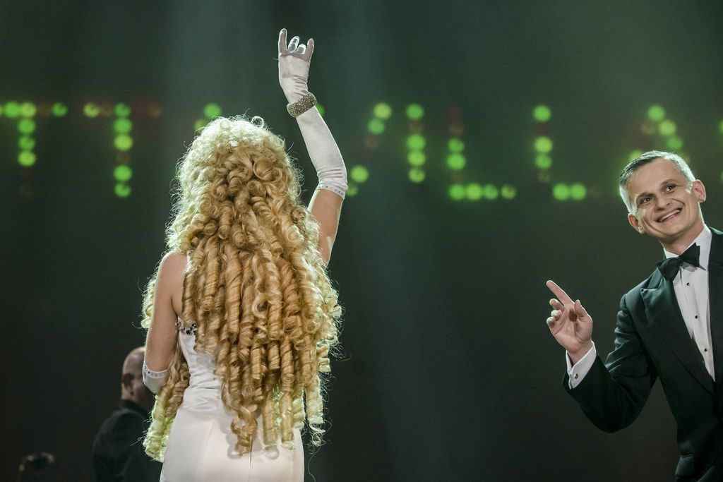 Tyłem do publiczności, na ciemnozielonym tle z błyszczącymi literami, stoi artystka stylizowana na Violettę Villas. Prawą rękę ma uniesioną wysoko ku górze, ubrana jest w białą, obcisłą, wieczorową suknię, na prawym przegubie ręki w długiej, białej rękawiczce, błyszczy gruba bransoletka. Kobieta ma bujną perukę kojarzącą się jednoznacznie z atrybutem Violetty Villas. Z prawej strony widać uśmiechniętego, szpakowatego mężczyznę w czarnym smokingu, białej koszuli, z muszką, wskazującego prawą dłonią w stronę artystki.
