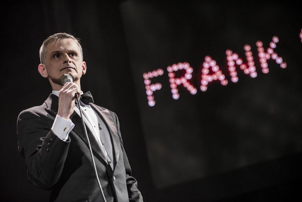 """Z mikrofonem w prawej dłoni stoi artysta kreujący rolę Franka Sinatry. Jest szpakowaty, ubrany w czarny smoking, białą koszulę i muszkę, patrzy w dal. Z prawej strony, w tle, widoczny jest różowy napis """"Frank""""."""