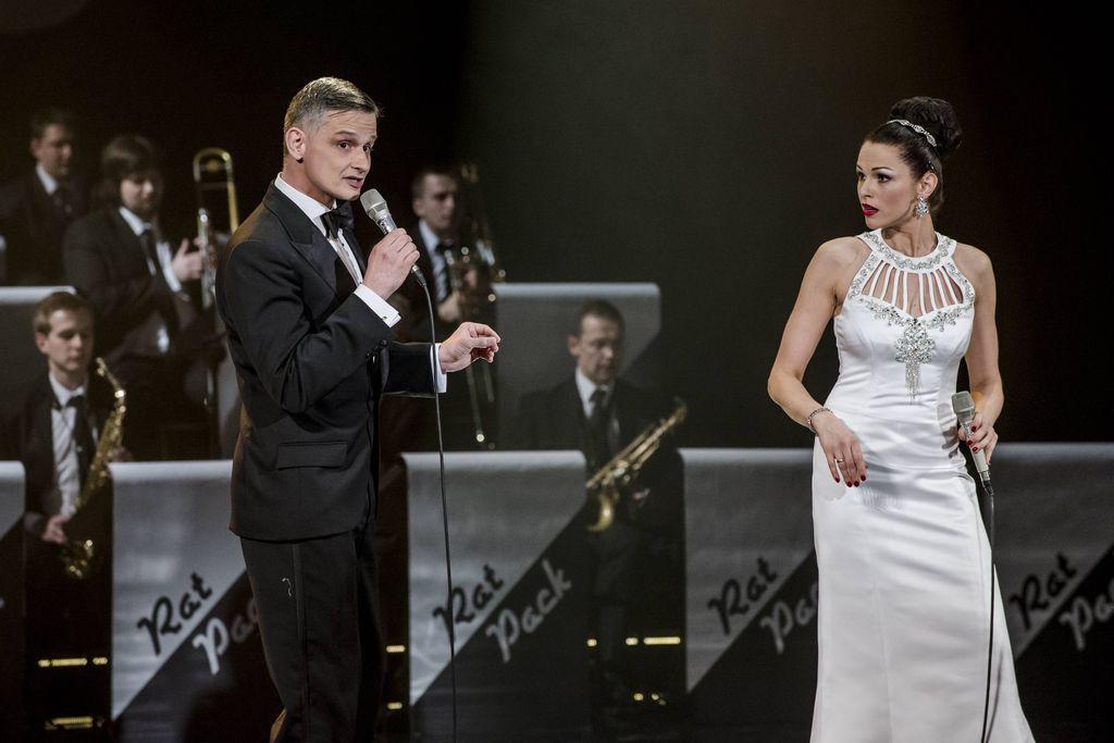 Dwoje artystów z mikrofonami w dłoniach. Z prawe strony znajduje się jedna z artystek tria Sisters, ma na sobie białą, wieczorową, obcisłą suknię, z dekoracyjnie obszytym dekoltem. Srebrne, błyszczące zdobienia harmonizują z biżuterią – bransoletkami, kolczykami i diademem w ciemnych, upiętych w kok, włosach. Patrzy na szpakowatego mężczyznę stojącego z lewej strony. Frank Sinatra śpiewa, lub mówi do mikrofonu, ubrany jest w ciemny smoking, białą koszulę i muszkę. W tle widoczni są muzycy big-bandu.