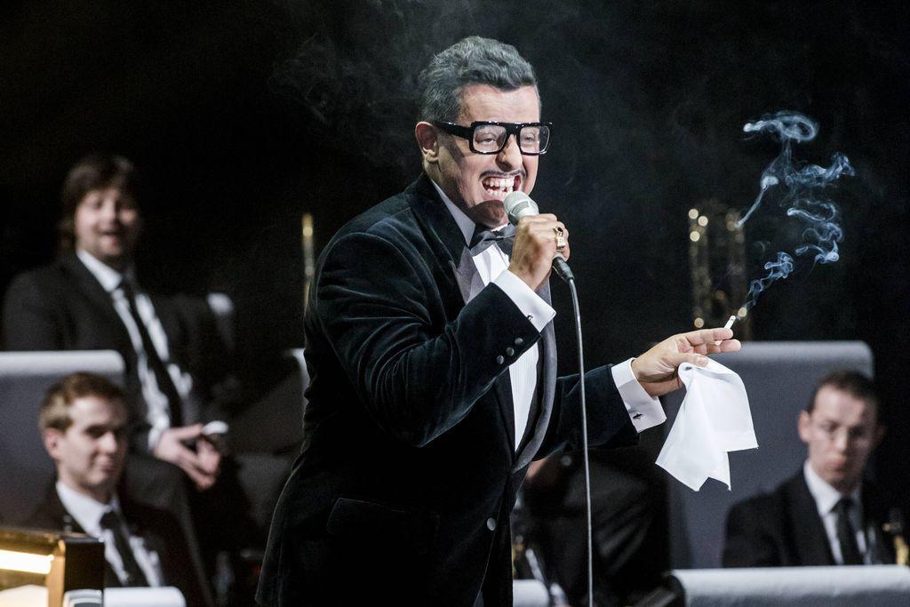 Na pierwszym planie stoi mężczyzna ubrany w elegancką, aksamitną, ciemną marynarkę, białą koszulę i muszkę. Sammy Davis Junior ekspresyjnie, z wyszczerzonymi zębami, śpiewa do trzymanego prawą dłonią mikrofonu, ma charakterystyczne okulary w czarnej oprawce i cienki wąsik. W lewej dłoni ma zapalonego papierosa i białą chusteczkę. W tle widoczni są muzycy big-bandu.