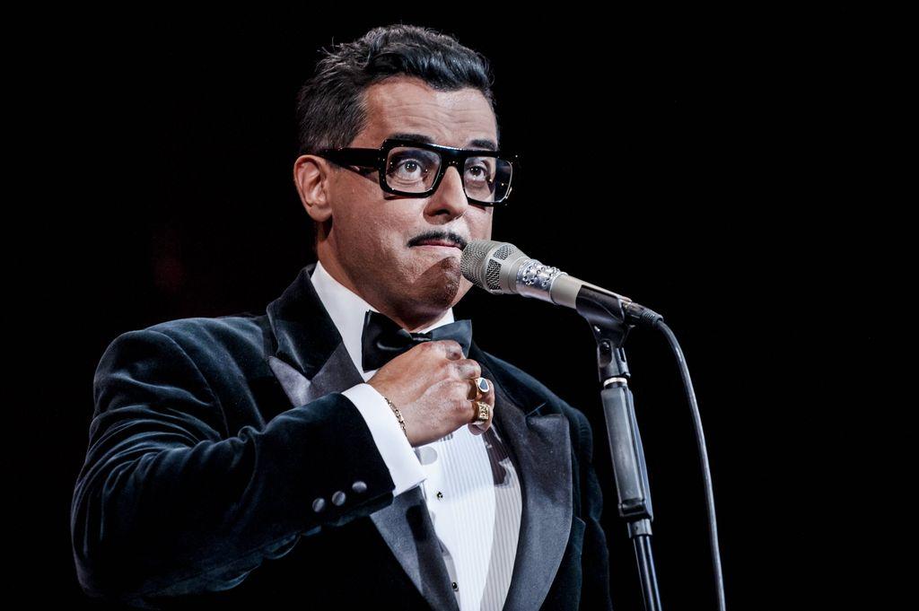 Cały kadr zajmuje wizerunek artysty, kreującego rolę Sammy`ego Davisa Juniora. Stoi przy mikrofonie, jest ubrany w elegancką, aksamitną, ciemną marynarkę i białą koszulę. Prawą dłoń, z sygnetami na najmniejszym i serdecznym palcu, kieruje ku muszce. Sammy Davis Junior mówi, lub śpiewa do mikrofonu, ma charakterystyczne okulary w czarnej oprawce i cienki wąsik.