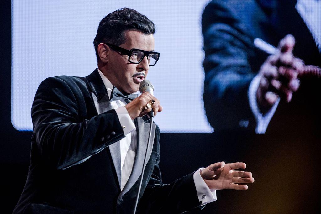 Cały kadr zajmuje wizerunek artysty, kreującego rolę Sammy`ego Davisa Juniora. Stoi z mikrofonem w prawej dłoni, jest ubrany w elegancką, aksamitną, ciemną marynarkę i białą koszulę. Na najmniejszym i serdecznym palcu prawej dłoni widać sygnety. Sammy Davis Junior mówi, lub śpiewa do mikrofonu, ma charakterystyczne okulary w czarnej oprawce i cienki wąsik. Tło tworzy ekran z wyświetlonym fragmentem postaci.