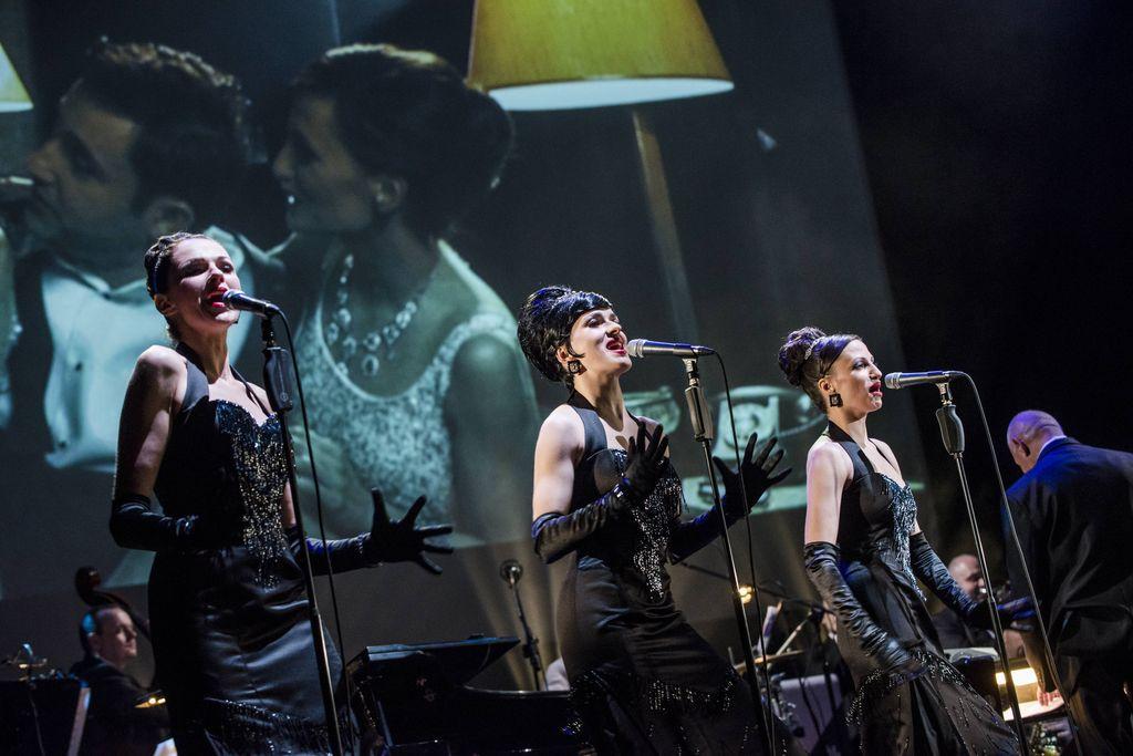 Trio śpiewających artystek stoi przy mikrofonach. Sisters ubrane są w wieczorowe, obcisłe, czarne, wydekoltowane suknie, mają odkryte ramiona, długie rękawiczki, błyszczącą biżuterię, diademy upięte przy dużych kokach. Za nimi widać muzyków big-bandu, a u góry, na dużym ekranie wyświetlane są mniej formalne sceny z bohaterami spektaklu.