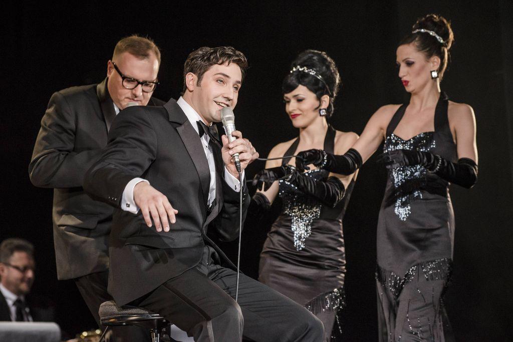 Na pierwszym planie widoczny jest ciemnowłosy mężczyzna z mikrofonem w lewej dłoni. Dean Martin śpiewa, lub mówi do mikrofonu, ubrany jest w smoking, ma białą koszulę i muszkę. Za nim stoi Konferansjer w okularach, obok niego dwie artystki z tria Sisters, ubrane w wieczorowe, obcisłe, czarne, wydekoltowane suknie. Mają odkryte ramiona, długie, czarne rękawiczki, błyszczącą biżuterię, diademy upięte przy dużych kokach.