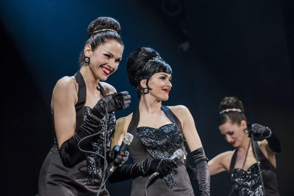Trio uśmiechniętych artystek, z mikrofonami w dłoniach, na ciemnym tle. Sisters ubrane są w wieczorowe, obcisłe, czarne, wydekoltowane suknie, mają odkryte ramiona, długie rękawiczki, błyszczącą biżuterię, diademy upięte przy dużych kokach.