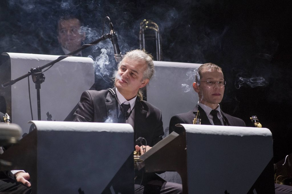 Na pierwszym planie dwaj muzycy z wieloosobowej orkiestry stylizowanej na swingowy big-band. Siedzą przed pulpitami, w stronę muzyka po lewej skierowany jest mikrofon. Wydmuchuje on dym z zapalonego papierosa. Ubrani są w garnitury, jasne koszule, krawaty. Nad nimi widnieją kolejne pulpity i - w nieostrości oraz papierosowym dymie – jeszcze jeden muzyk.
