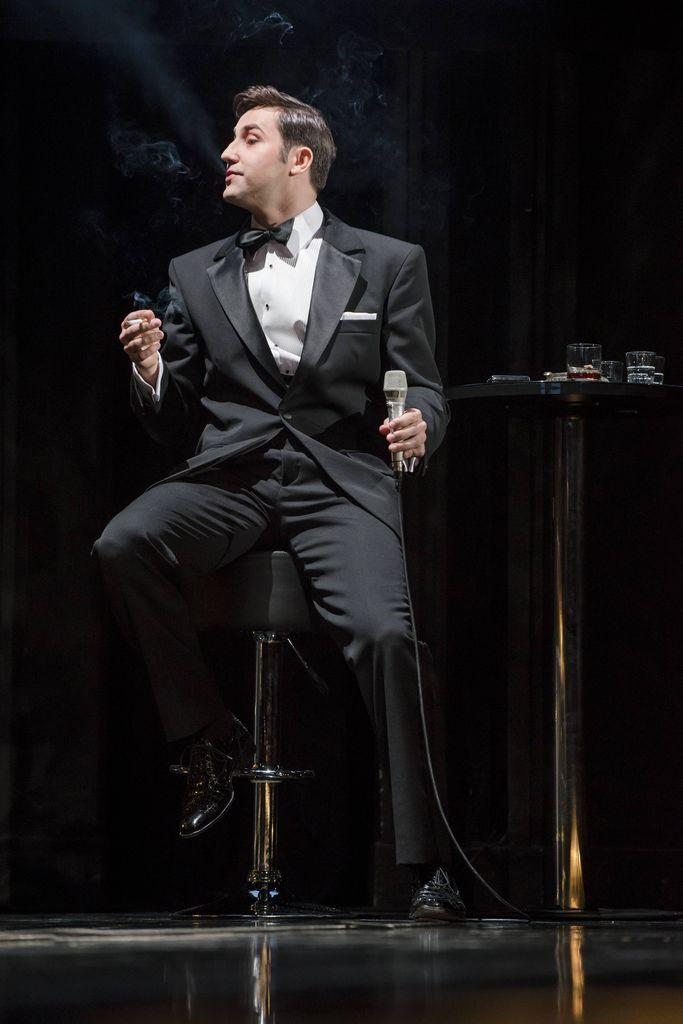 Ciemnowłosy mężczyzna z mikrofonem w lewej ręce i zapalonym papierosem w prawej dłoni, siedzi na wysokim krześle, zwrócony profilem w lewą stronę. Dean Martin ubrany jest w smoking, ma białą koszulę i muszkę, wydmuchuje dym papierosowy. Przy nim, z prawej strony, stoi wysoki stolik, ze szklaneczkami na blacie.