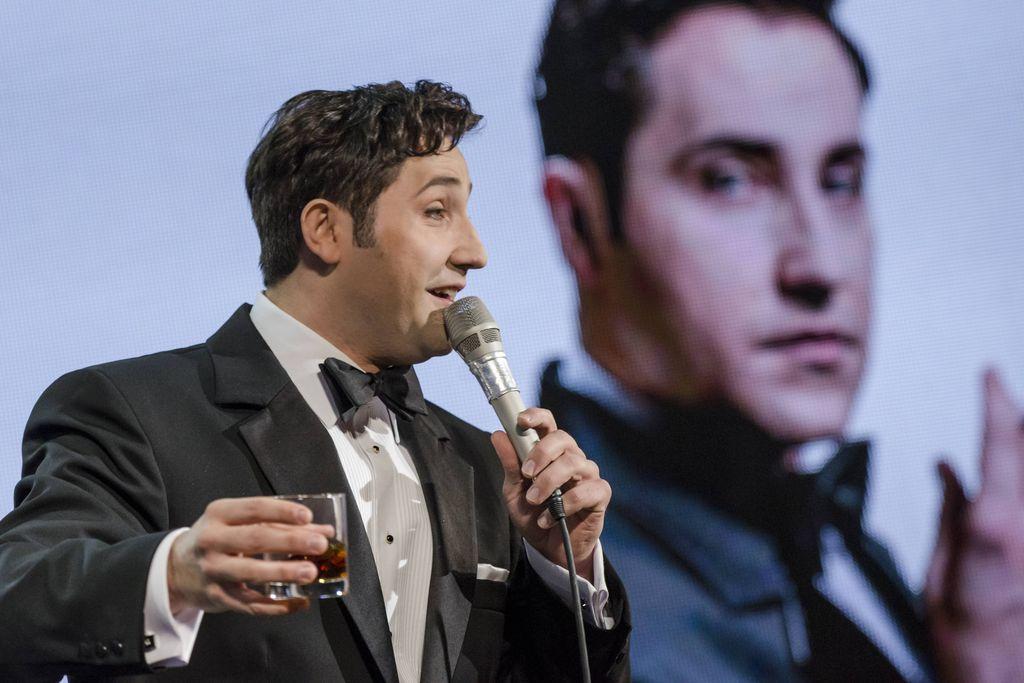 Z lewej strony widoczny jest ciemnowłosy mężczyzna z mikrofonem w lewej ręce i szklaneczką z brązowym, przejrzystym płynem, w prawej dłoni. Dean Martin śpiewa, lub mówi do mikrofonu, ubrany jest w smoking, ma białą koszulę i muszkę. W tle, w nieostrości znajduje się biały ekran, wyświetla się na nim twarz artysty kreującego Deana Martina.