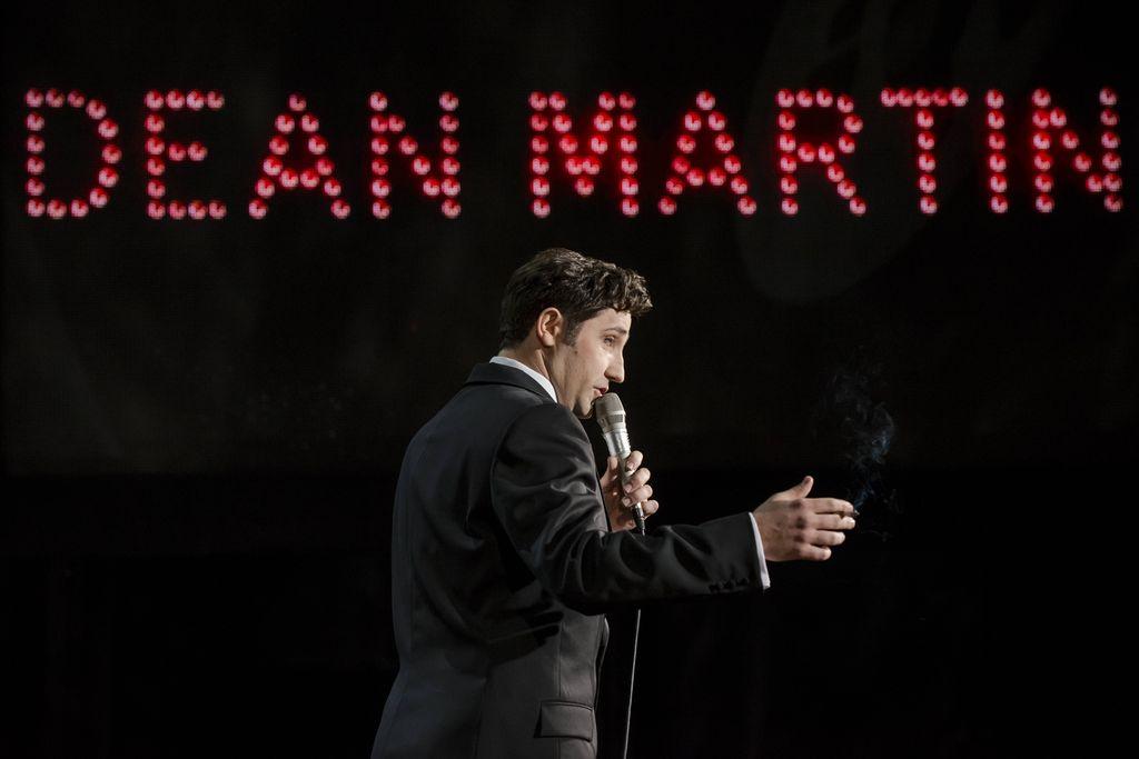 """Na pierwszym planie widoczny jest ciemnowłosy mężczyzna z mikrofonem w lewej dłoni. Dean Martin śpiewa, lub mówi do mikrofonu, ubrany jest w smoking i białą koszulę. Stoi bokiem, prawym profilem zwrócony w prawą stronę, w dłoni trzyma zapalonego papierosa. W tle widoczne są duże, czerwone litery tworzące napis """"Dean Martin""""."""