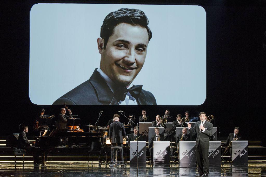 Na scenie widać cały, wieloosobowy big-band, z dyrygentem odwróconym tyłem do publiczności. Z prawej strony stoi Dean Martin, w czarnym smokingu, z mikrofonem w lewej ręce, śpiewa albo mówi. U góry znajduje się duży, biały ekran, wyświetlana jest na nim podobizna artysty kreującego rolę Deana Martina.