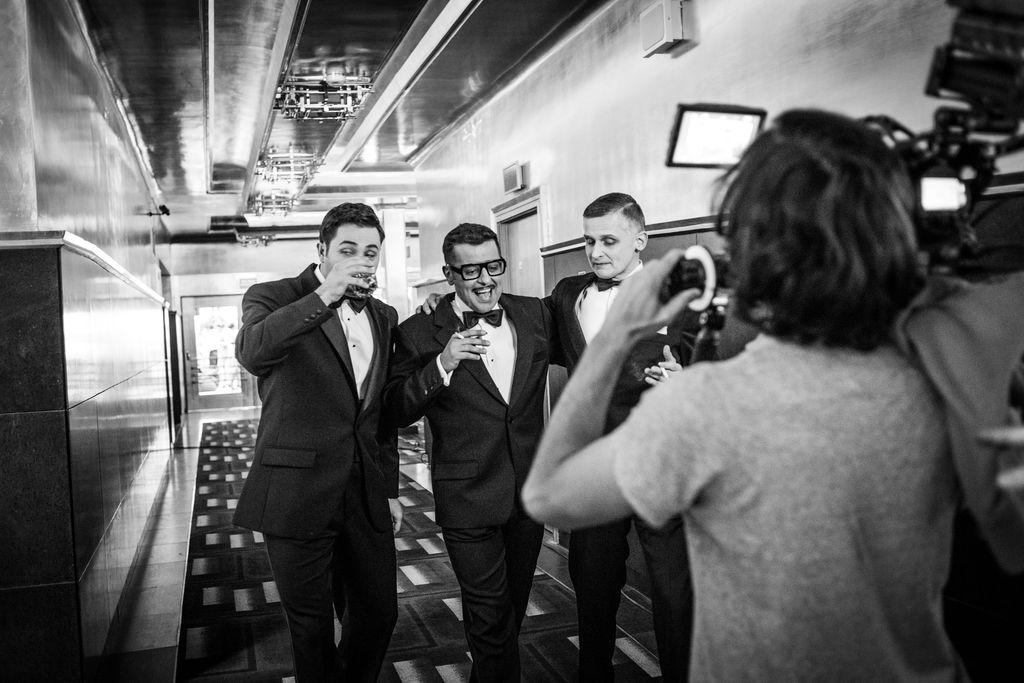 Czarno-białe zdjęcie. Trzej mężczyźni idą holem teatralnym. Ubrani są w eleganckie garnitury i białe koszule z muszkami. Sammy Davis Junior i Frank Sinatra trzymają w dłoniach zapalone papierosy, Dean Martin – w prawej dłoni trzyma szklankę z napojem, podnosi ją ku ustom. Idą w stronę widocznego od tyłu człowieka, obsługującego archaiczną kamerę.