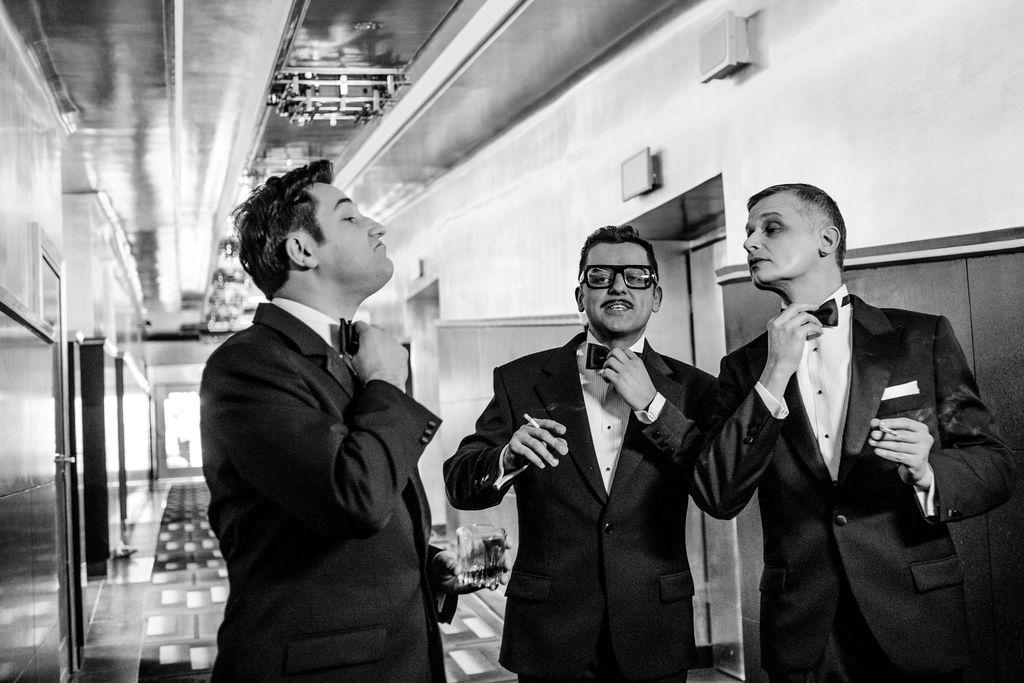 Czarno-białe zdjęcie. Trzej mężczyźni stoją w holu teatralnym. Ubrani są w eleganckie garnitury i białe koszule, wszyscy wykonują gest poprawiania muszki. Sammy Davis Junior i Frank Sinatra trzymają w dłoniach zapalone papierosy, Dean Martin – szklankę z napojem.
