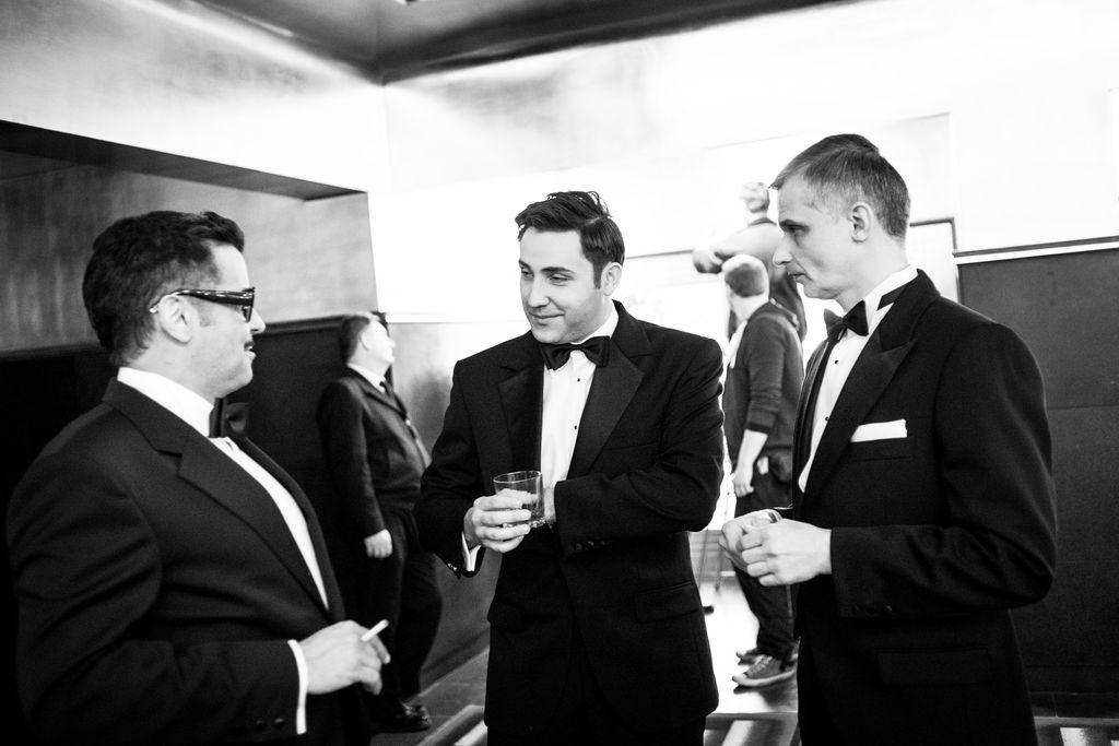 Czarno-białe zdjęcie. Trzej mężczyźni stoją w holu teatralnym. Ubrani są w eleganckie garnitury i białe koszule oraz muszki. Z lewej strony kadru stoi Sammy Davis Junior, trzyma w prawej dłoni zapalonego papierosa, zwraca się w rozmowie w kierunku Deana Martina, trzymającego szklankę. Przygląda im się stojący z prawej Frank Sinatra. W tle widać kilka osób.