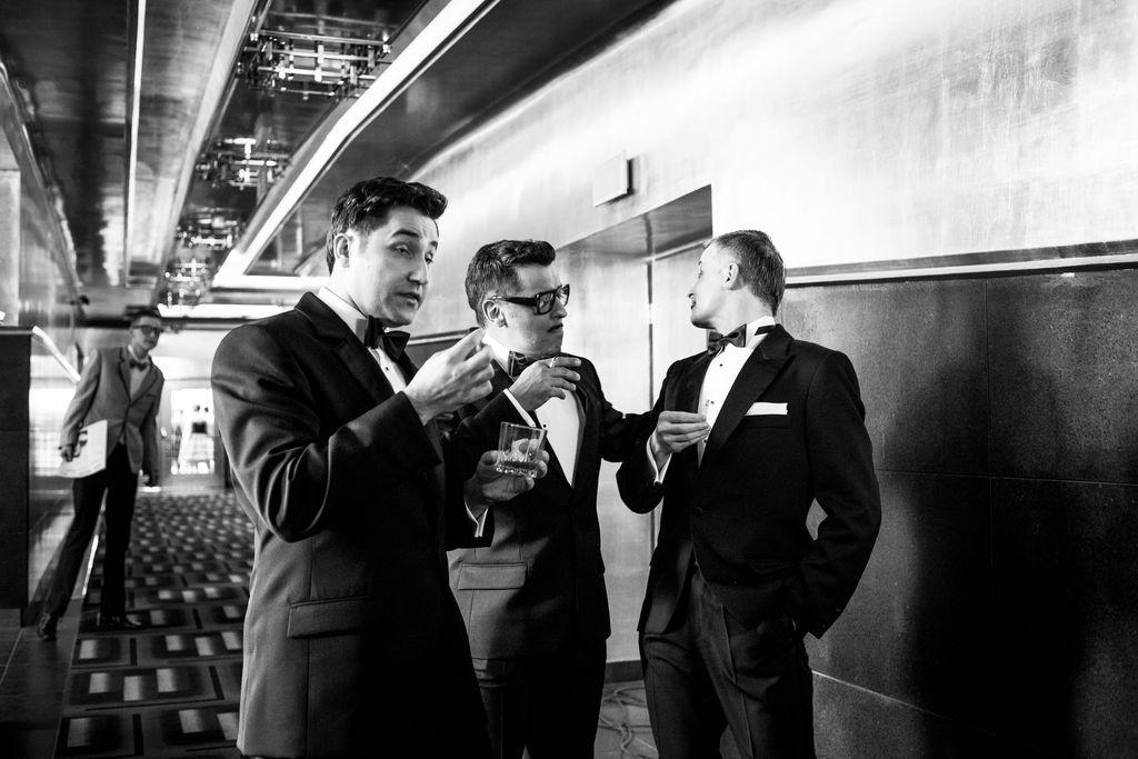 Czarno-białe zdjęcie. Trzej mężczyźni stoją w holu teatralnym. Ubrani są w eleganckie garnitury i białe koszule. Sammy Davis Junior i Frank Sinatra trzymają w dłoniach zapalone papierosy, Dean Martin – szklankę z napojem. W tle widoczny jest mężczyzna, ku któremu zwraca głowę artysta występujący w roli Franka Sinatry.