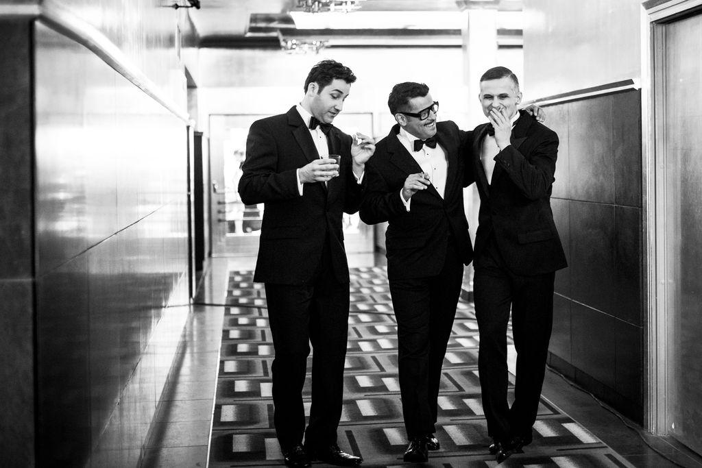 Czarno-białe zdjęcie. Trzej mężczyźni stoją w holu teatralnym. Ubrani są w eleganckie garnitury i białe koszule z muszkami. Sammy Davis Junior i Frank Sinatra trzymają w dłoniach zapalone papierosy, Dean Martin – szklankę z napojem.