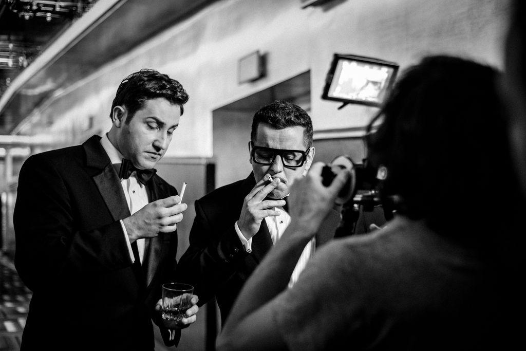 Czarno-białe zdjęcie przedstawia dwóch mężczyzn znajdujących się w holu teatru. Stoją przed obiektywem widocznego od tyłu fotografa, jego sylwetka zajmuje prawą część kadru. Dean Martin patrzy na papierosa trzymanego w palcach prawej, uniesionej dłoni, w lewej ręce ma szklankę. Sammy Davis Junior zaciąga się papierosem. Obydwaj ubrani są w garnitury, białe koszule i muszki.