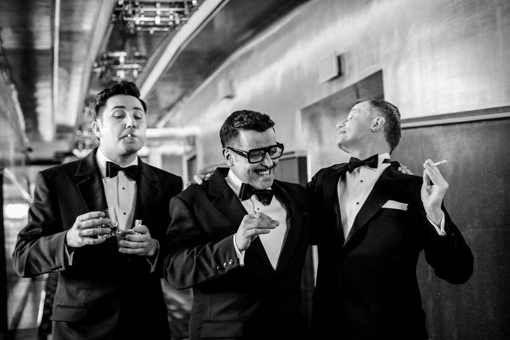 Czarno-białe zdjęcie. Trzej mężczyźni stoją w holu teatralnym. Ubrani są w eleganckie garnitury i białe koszule. Sammy Davis Junior i Frank Sinatra trzymają w dłoniach zapalone papierosy, Dean Martin – papierosa ma w ustach, a w prawej dłoni trzyma szklankę z napojem. Artysta występujący w roli Franka Sinatry zwraca głowę w tył, jakby mówił do kogoś usytuowanego za nimi.
