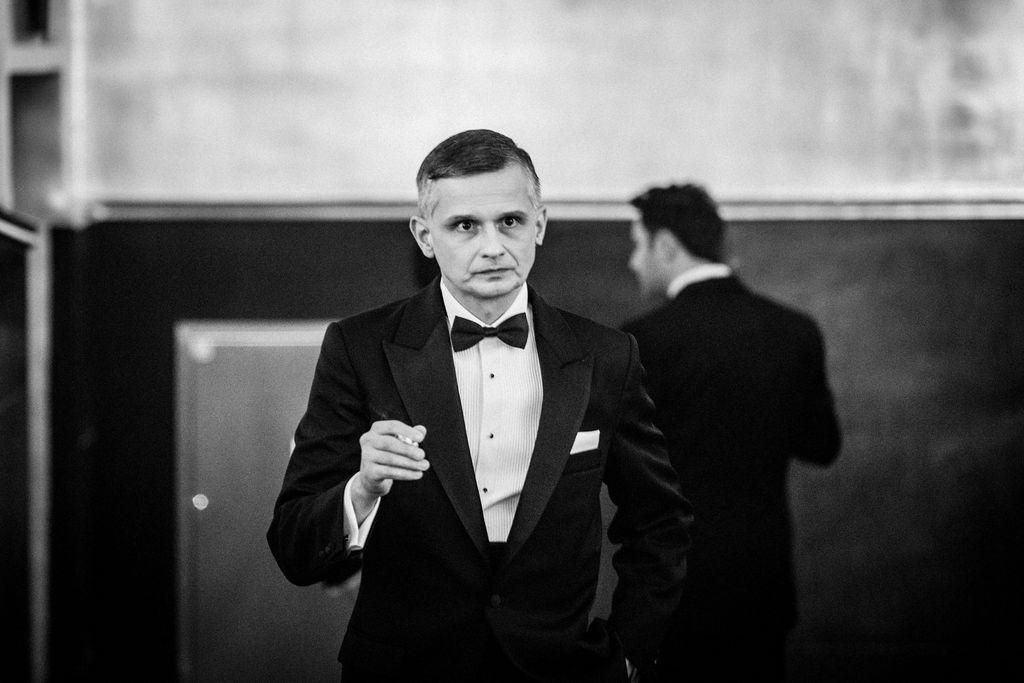 Czarno-biały portret artysty kreującego rolę Franka Sinatry. Szpakowaty mężczyzna stoi w holu teatru, patrzy przed siebie. Jest ubrany w garnitur, białą koszulę z muszką, w prawej dłoni trzyma zapalonego papierosa. W tle, w nieostrości, widać sylwetkę Deana Martina.