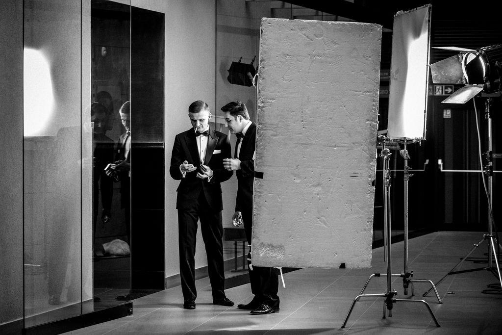 W teatralnym foyer stoją dwaj mężczyźni, jeden, z zapalonym papierosem w ustach, trzyma coś w dłoni, drugi – ze szklanką w lewej dłoni, spogląda w kierunku trzymanego przedmiotu. Obaj ubrani są w eleganckie garnitury, mają białe koszule i muszki. Obok nich rozstawiony jest sprzęt fotograficzny. Zdjęcie jest czarno-białe.