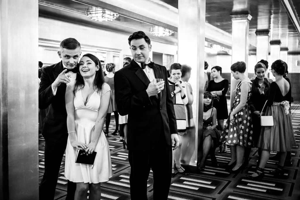 Czarno-białe zdjęcie przedstawia foyer teatru. Z lewej strony znajdują się trzy osoby: pomiędzy dwoma mężczyznami w garniturach, białych koszulach i muszkach, stoi młoda, szeroko uśmiechnięta dziewczyna w jasnej, lekkiej sukience, trzymająca w opuszczonych dłoniach zeszyt i długopis. Szpakowaty mężczyzna, czyli Frank Sinatra, patrzy w stronę fotografa i wskazuje palcem dziewczynie ten kierunek. Ciemnowłosy mężczyzna obok, patrzy spod opuszczonych powiek w ich stronę, w prawej dłoni trzyma szklankę. W tle widać dużą grupę młodych kobiet, rozmawiających ze sobą.