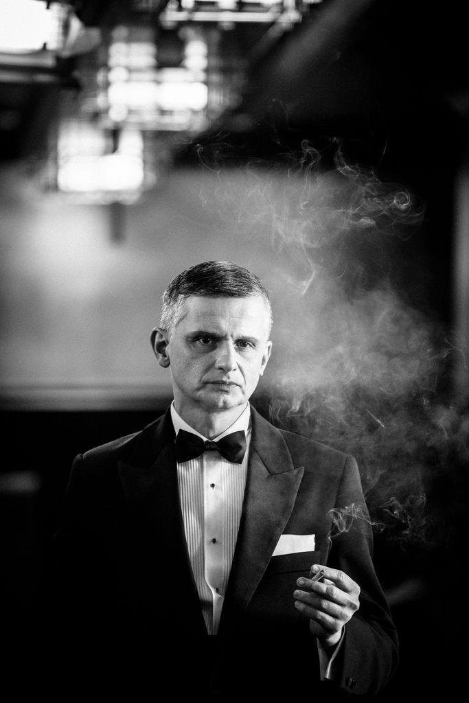 Czarno-biały portret artysty kreującego rolę Franka Sinatry. Szpakowaty, zadumany mężczyzna stoi w holu teatru, jest ubrany w garnitur, białą koszulę z muszką, w lewej dłoni trzyma zapalonego papierosa. Spowija go dym.