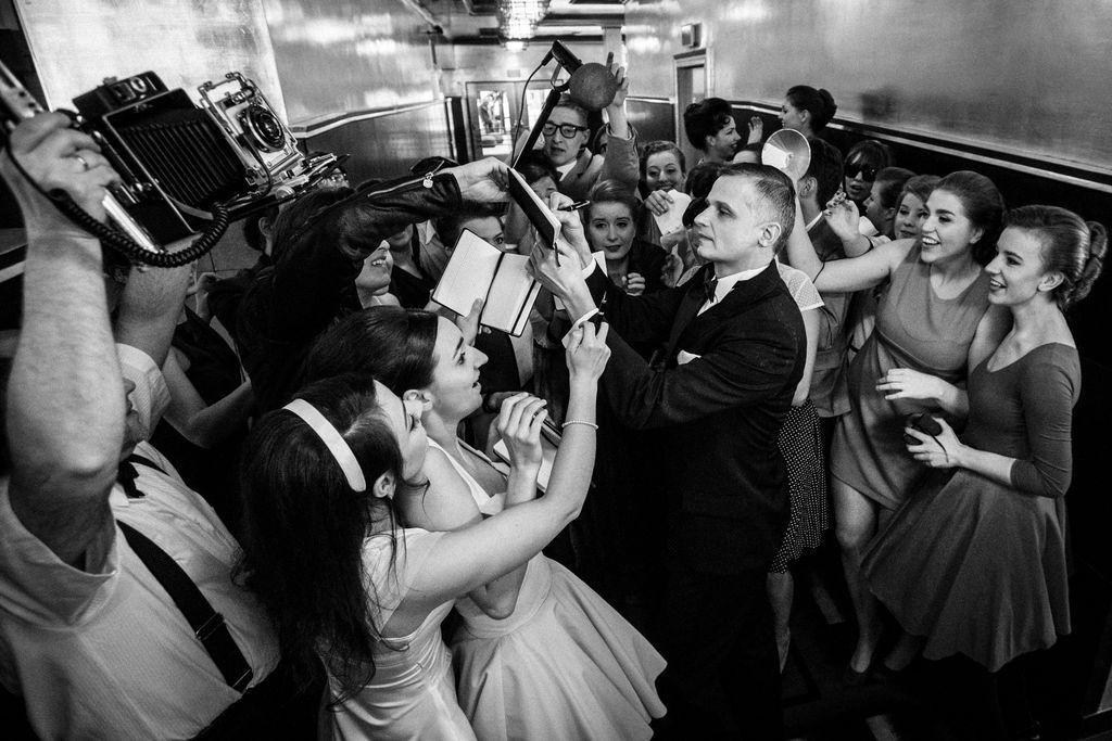 Na czarno-białym zdjęciu grupa młodych kobiet oblega w foyer teatralnym Franka Sinatrę. Artysta rozdaje autografy, kobiety są podekscytowane, radosne. Z lewej strony widać mężczyzn unoszących w górę starodawne aparaty fotograficzne oraz mikrofon na statywie. Zarówno stroje, jak i rodzaj sprzętu fotograficznego wskazują, że jest to sytuacja stylizowana na lata 60-te XX wieku.