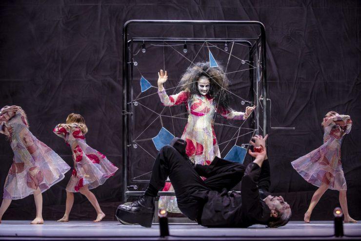 W centrum Giulia, kobieta ze szkła (Magdalena Szczerbowska). Stoi wewnątrz urządzenia z metalowych prętów i luster z korbą i żarówkami. Uśmiecha się upiornie i unosi dłonie. Przed Giulią, na pierwszym planie widać monstrum. Leży na plecach ze spazmatycznie wyciągniętymi, zgiętymi kończynami. Po prawej i lewej stronie tancerki w witrażowych sukniach. Uciekają, osłaniając twarze ramionami.