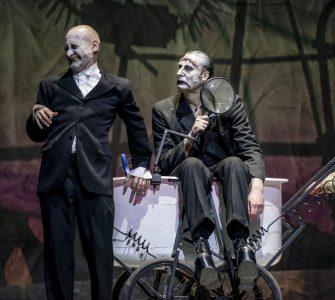 Od lewej Wiktor Frankenstein (Kiljan), monstrum (Studniak) i Igor (Picher). Monstrum siedzi na wózku laboratoryjnym, trzyma szkło powiększające. Wiktor oparty o wózek plecami, krzywi twarz. Obydwoje patrzą w jednym kierunku. Igor wychodzi z kadru z prawej strony.
