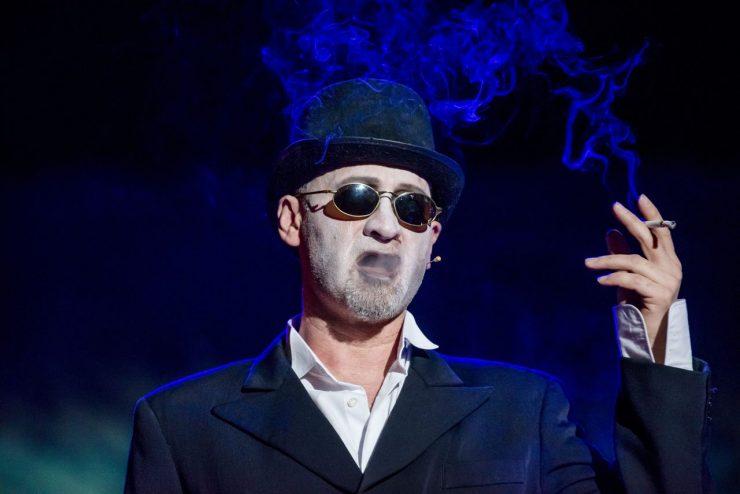 Zbliżenie na Wiktora Frankensteina (Mariusz Kiljan). Ubrany w białą koszulę i czarną marynarkę, melonik i ciemne okularu. W uniesionej dłoni trzyma papierosa. Nad jego głową unosi się chmura papierosowego dymu.