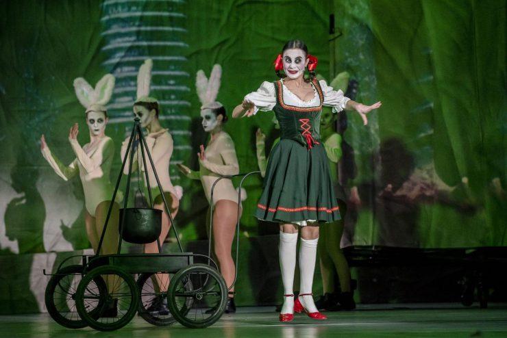 Na pierwszym planie Agata, żona Ślepca (Justyna Antoniak). Biała koszula, podkolanówki i halka, zielony gorset i spódnica do kolan. Czerwone wstążki w warkoczach, lakierki i detale stroju. Stoi na palcach, unosi ręce, uśmiecha się. Po lewej stronie wózek, a na nim żeliwny kociołek wiszący na stojaku. W tle trzy tancerki – zajączki.