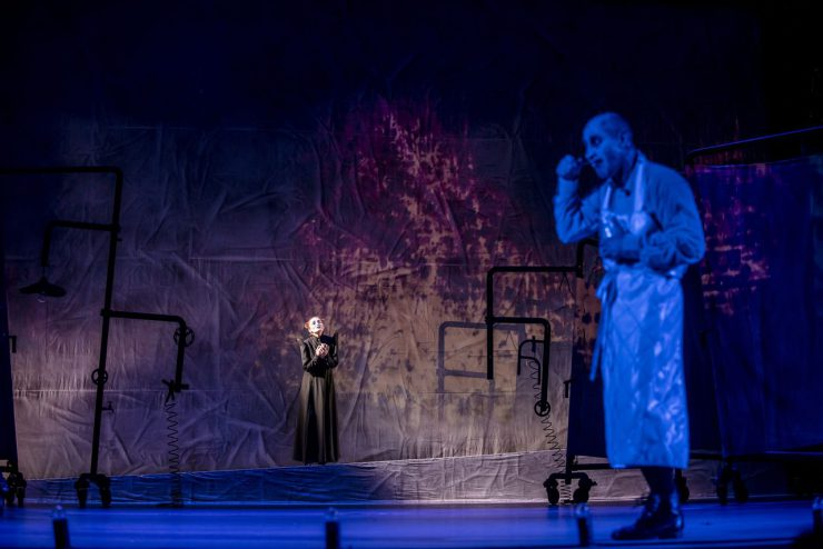 Na pierwszym planie Wiktor Frankenstein (Mariusz Kiljan). Postać rozmyta, oświetlona na niebiesko. W oddali matka Wiktora (Justyna Szafran). Ubrana w czarną suknię ma dłonie złożone na piersi i oczy wzniesione ku górze. Postać matki w perspektywie wydaje się niewielka, ale to ona skupia uwagę. W tle dominują odcienie błękitu i fioletu.