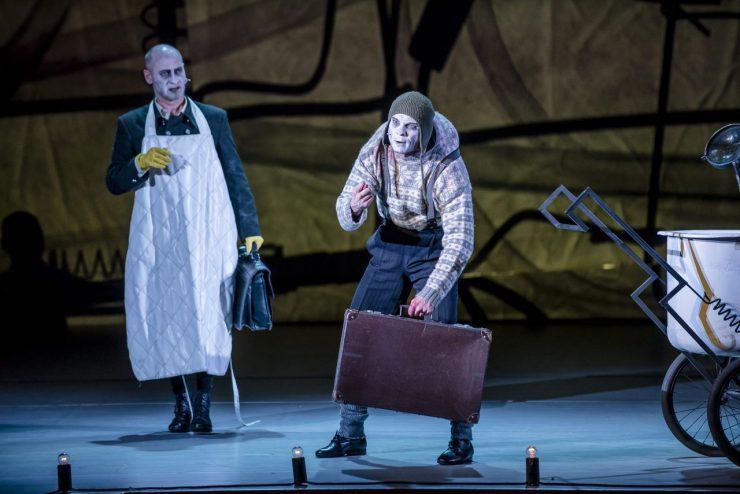 Od lewej: Wiktor Frankenstein (Mariusz Kiljan) i Igor (Bartosz Picher). Wiktor jest ubrany w biały fartuch i żółte rękawice ochronne, niesie czarną, skórzaną teczkę. Garbaty pomocnik Frankensteina nosi wełnianą czapkę pilotkę, wzorzysty sweter i spodnie na szelkach. Dźwiga dużą, brązową walizkę. Ściska kciuk między wskazującym i środkowym palcem dłoni w szyderczym geście. Z prawej strony widać fragment wózka laboratoryjnego.