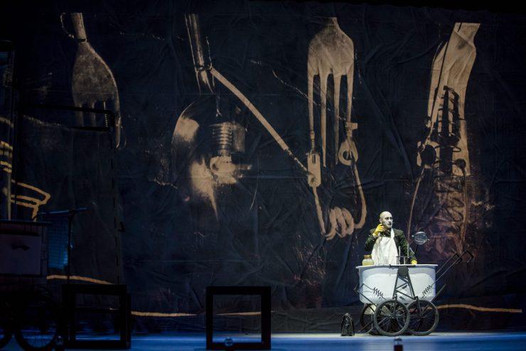 Wiktor Frankenstein (Mariusz Kiljan) w fartuchu i żółtych gumowych rękawicach stoi przy laboratoryjnym wózku. Na blacie słój, próbówki i szkło powiększające. Obok wózka skórzana teczka. W tle wizualizacja z instalacją ze sztućców, sprężyn i drutów na strukturze wygniecionego materiału.