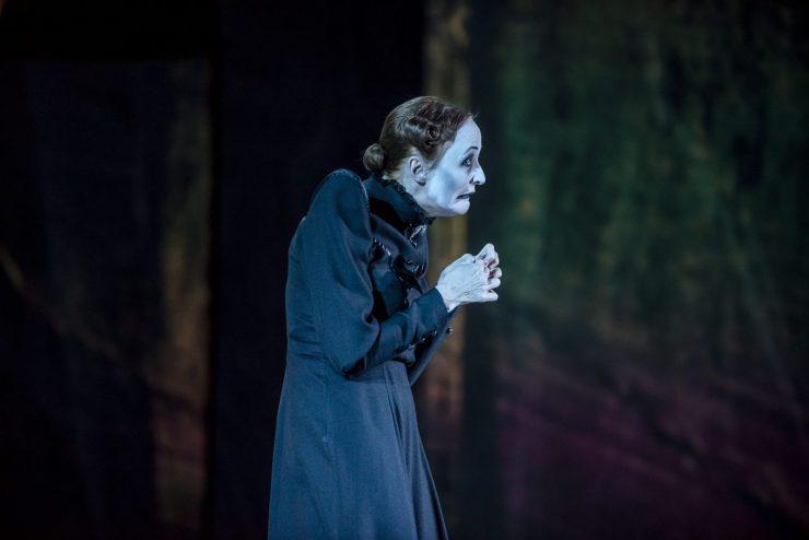 Zbliżenie na matkę Wiktora Frankensteina (Justyna Szafran) - ujęcie z profilu. Postać ubrana w czarną suknię ze stójką, włosy spięte w kok nad karkiem, ozdobny lok przy skroni. Ma zgarbioną sylwetkę i wykrzywioną twarz, unosi złożone dłonie na wysokość piersi.
