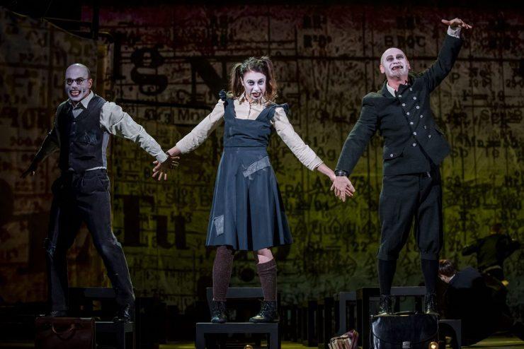 Od lewej: Henryk Clerval (Mikołaj Woubishet), Elżbieta Schneider (Helena Sujecka) i Wiktor Frankenstein (Mariusz Kiljan). Ubrani w szkolne mundurki stoją na krzesłach, zwróceni do publiczności i trzymają się za ręce. W tle wizualizacja, którą tworzą układ okresowy pierwiastków i wzory matematyczne.