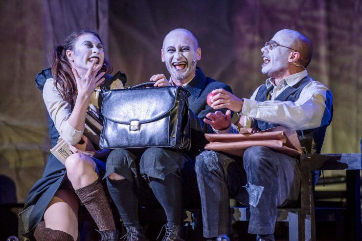 Od lewej: Elżbieta Schneider (Helena Sujecka), Wiktor Frankenstein (Mariusz Kiljan) i Henryk Clerval (Mikołaj Woubishet). Ubrani w mundurki siedzą w szkolnej ławce. Są zwróceni do siebie nawzajem, śmieją się. Wiktor i Henryk trzymają na kolanach skórzane teczki.